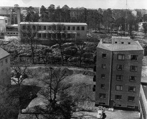 Vy av Spetsberget där Ekensbergsskolan ligger på kullen. Till vänster Vårvägen med ännu ofullbordad parkeringsplats. Ca 1959.