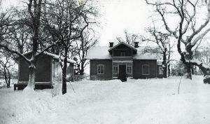 """Ekensberg, den gula huvudbyggnaden i den vackra ekbacken. Byggnadsår är okänt. Gården låg där brandstationen, Vårvägen och Sommarvägens hus ligger. Den ägdes av Max Wibom på Huvudsta gård. Gränsen mellan Huvudsta och Råsunda gick utefter Hagavägens sträckning. Idag är vägen omdöpt till Ekensbergsvägen. Från 1913 arrenderades gården av familjen Nyberg och före det familjen Wahlström. Då lär huvudbyggnadens hus haft jordgolv. T.v. ser vi det hus som kallades """"mjölkboa"""". Där lär fru Nyberg sålt mjölk."""