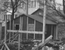 Förstoring ur bild. En bit framför och mellan Vårvägen 5 och 7 låg lada och häststall ända fram till 1957. Dessa användes under byggandet av brandstationen som arbetarbaracker. Bakom dessa skymtar vi Vårvägens nybyggda fastighet.