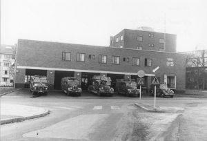Brandstationen 1957 med Vårvägen skymtande till vänster. Nypolerade brandbilar visas stolt upp.