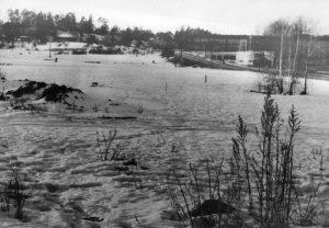 """Vinterbild. Hagavägen till höger. Till vänster Ekensbergs gård. Stora ladan syns. Bakom den ser vi """"mjölkboa"""". Ca 1930."""