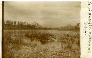 """Rudsjön """"Is på Rudsjön Vintern 1916"""". Till höger på bilden Ekensberg. Torpställena i närheten hette Rudsjödal och Rudtorp, intill fanns Rudagatan ,Villa Ruda och Villa Rudboda. Rudsjögatan existerar än i dag. Namnen berättar om riklig förekomst av rudor och att karpfisken var ett välkommet tillskott i hushållet hos de fattiga industriarbetarfamiljer som på artonhundratalet bebyggde och bebodde municipalsamhällena Nya Huvudsta och Hagalund."""