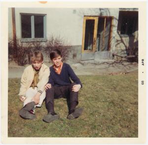 Bild från gården en vårdag år 1968. Kompisarna Olle Sålder och Peter Nyström, båda i trean njuter av solen. Olle vann SM i gymnastik. Han brukade träna i både i brandstationens och Råsundaskolans gympasalar. Hans pappa var flygstyrman på SAS långlinjer över Atlanten. Fotot visar också Vårvägen-fastighetens originalfärg som var gråvitt ända fram till första halvan av 1980-talet. Foto: Kodak Instamatic-kamera, april 1968.